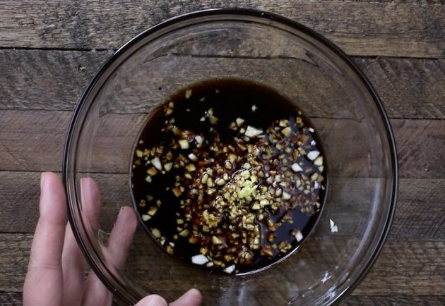 This photo shows making honey garlic sauce using soy sauce, honey and minced garlic in a small mixing bowl