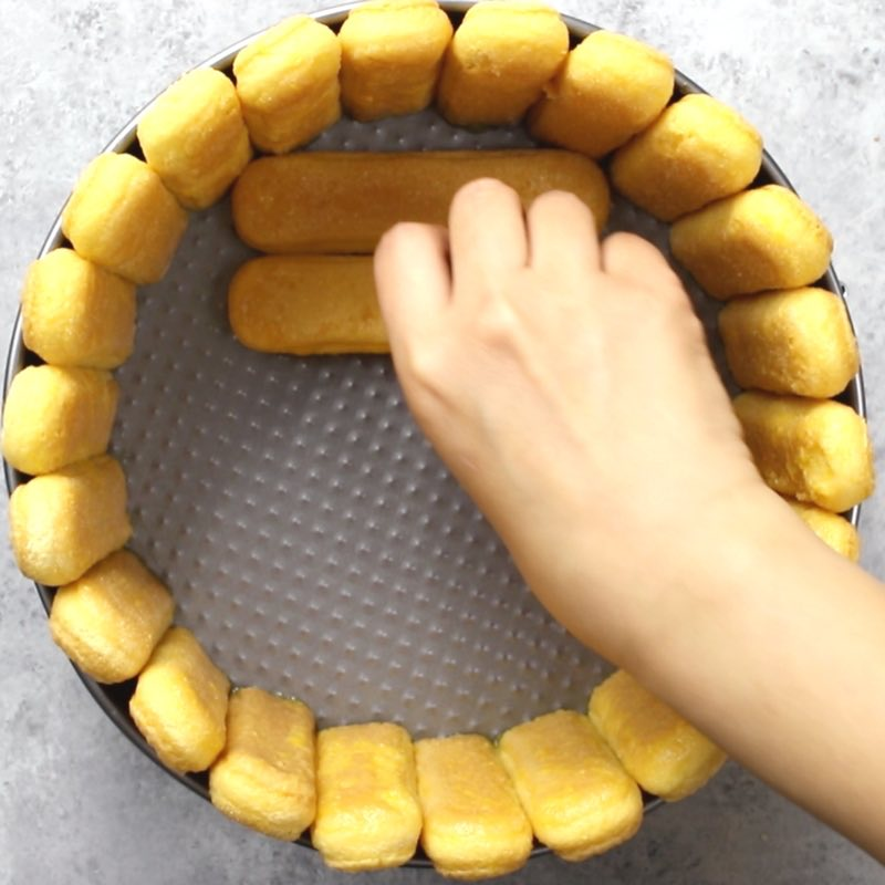 This photo shows how to arrange ladyfingers inside of a cake mold to make a Mango Cheesecake Charlotte