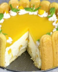 No Bake Mango Cheesecake – the most beautiful and unbelievably delicious charlotte-style mango cheesecake. All you need is some simple ingredients: mango juice, ladyfingers, cream cheese, sugar, whipped cream, mango, gelatin, and rum or triple sec. So Good! Perfect for a holiday party or a special occasion such as birthday and Mother's Day! No bake cheesecake. Dessert recipe. Vegetarian. Video Recipe | Tipbuzz.com