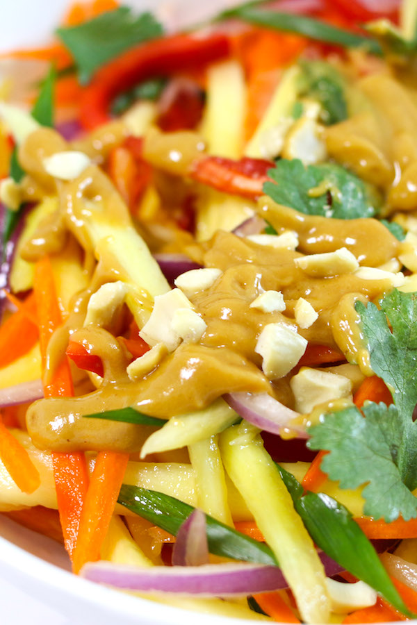 Closeup view of mango salad topped with chopped peanuts and drizzled with peanut dressing