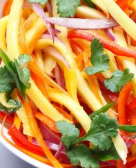 Mango Salad in a serving bowl for a quick summer salad recipe that everyone always loves! A rich and creamy Peanut Dressing is tossed with fresh mango, carrots, red bell pepper, red onions and crunchy peanuts to give you the most refreshing salad