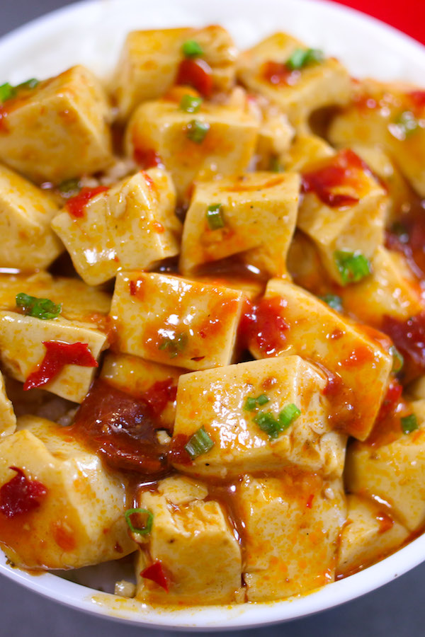 Mapo Tofu served in a rice bowl and topped with crushed szechuan peppercorns and minced green onion
