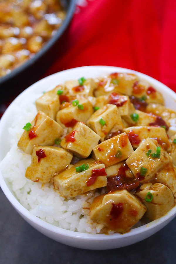 A serving of mapo tofu on a plate on a bed of steamed rice