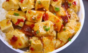 Mapo Tofu served in a rice bowl topped with crushed szechuan peppercorns and minced green onions