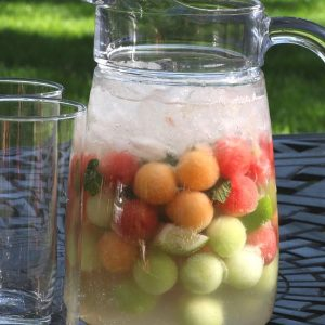 A pitcher of watermelon mojito with highball glasses - the perfect summer cocktail!