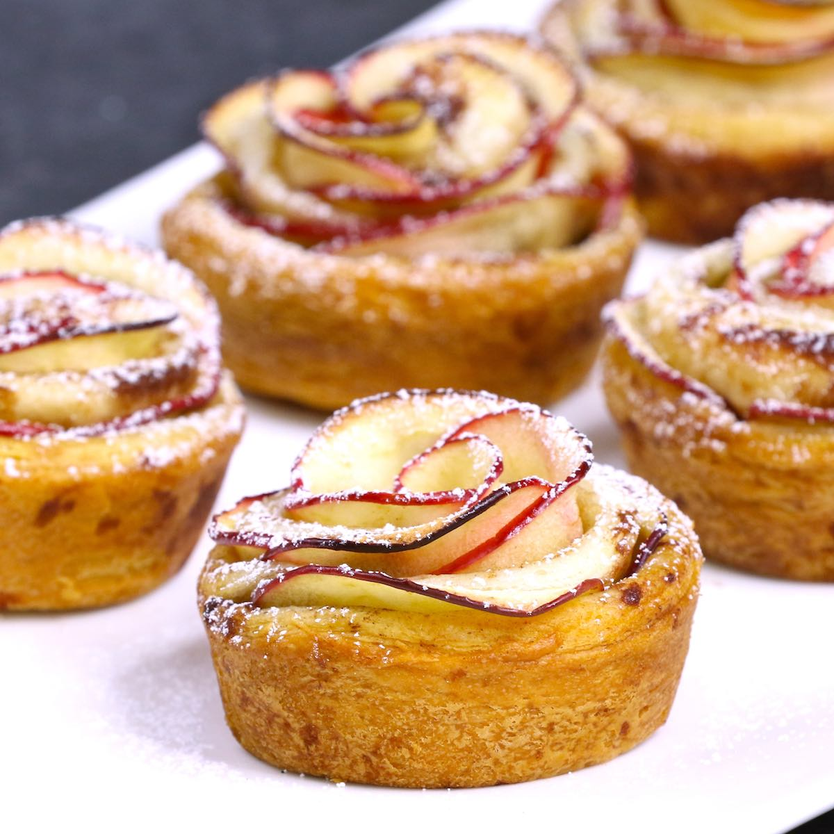 Apple rose tarts on a serving platter dusted with powdered sugar
