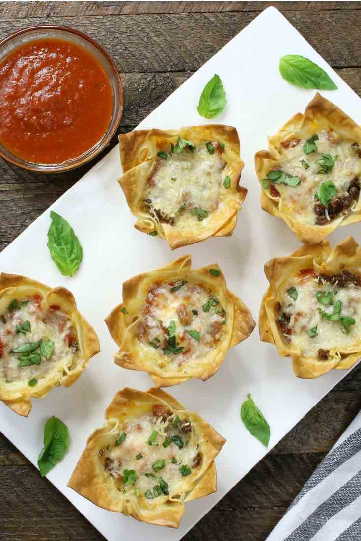 Mini Lasagna Cups: warm, crispy and cheesy handheld lasagna! Cooked ground beef, mozzarella, parmesan, ricotta, and pizza sauce baked inside of wonton wrappers in a muffin tin! The easiest lasagna you will ever make – the perfect snack, lunch or quick weeknight dinner! Quick and easy recipe. Party food, easy dinner. Video recipe.   Tipbuzz.com