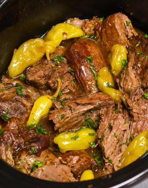 """This easy Mississippi Pot Roast is loaded with tender and juicy chuck roast! It's a """"dump and go"""" recipe made with a beef roast, pepperoncini peppers, au jus gravy mix, ranch dressing mix and butter. It's the BEST crock pot roast recipe which takes only 10 minutes to prepare and let the slow cooker do the rest!"""