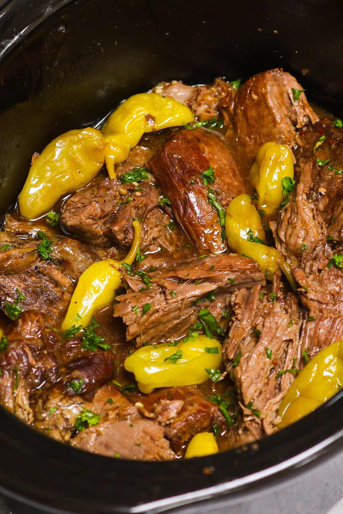 "This easy Mississippi Pot Roast is loaded with tender and juicy chuck roast! It's a ""dump and go"" recipe made with a beef roast, pepperoncini peppers, au jus gravy mix, ranch dressing mix and butter. It's the BEST crock pot roast recipe which takes only 10 minutes to prepare and let the slow cooker do the rest!"