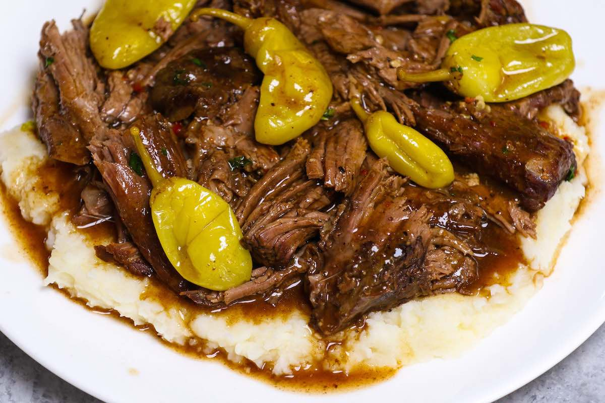 Mississippi pot roast served with gravy on mashed potatoes.