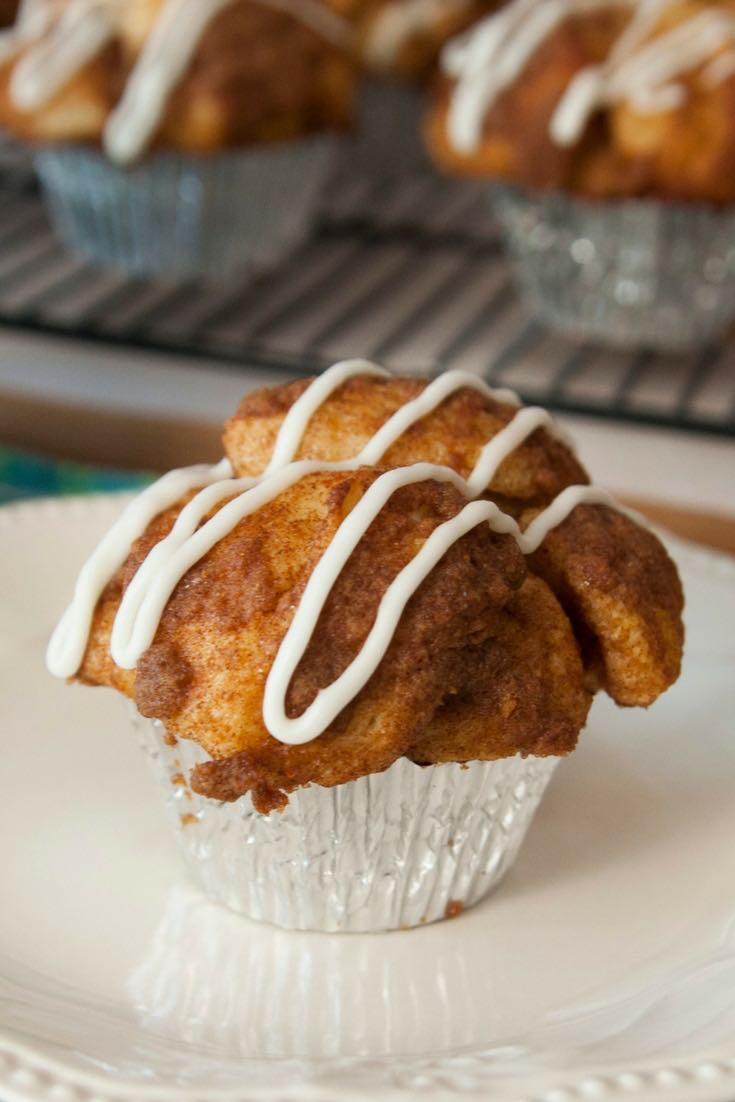 A freshly baked monkey bread muffin on a serving plate with icing drizzled on top