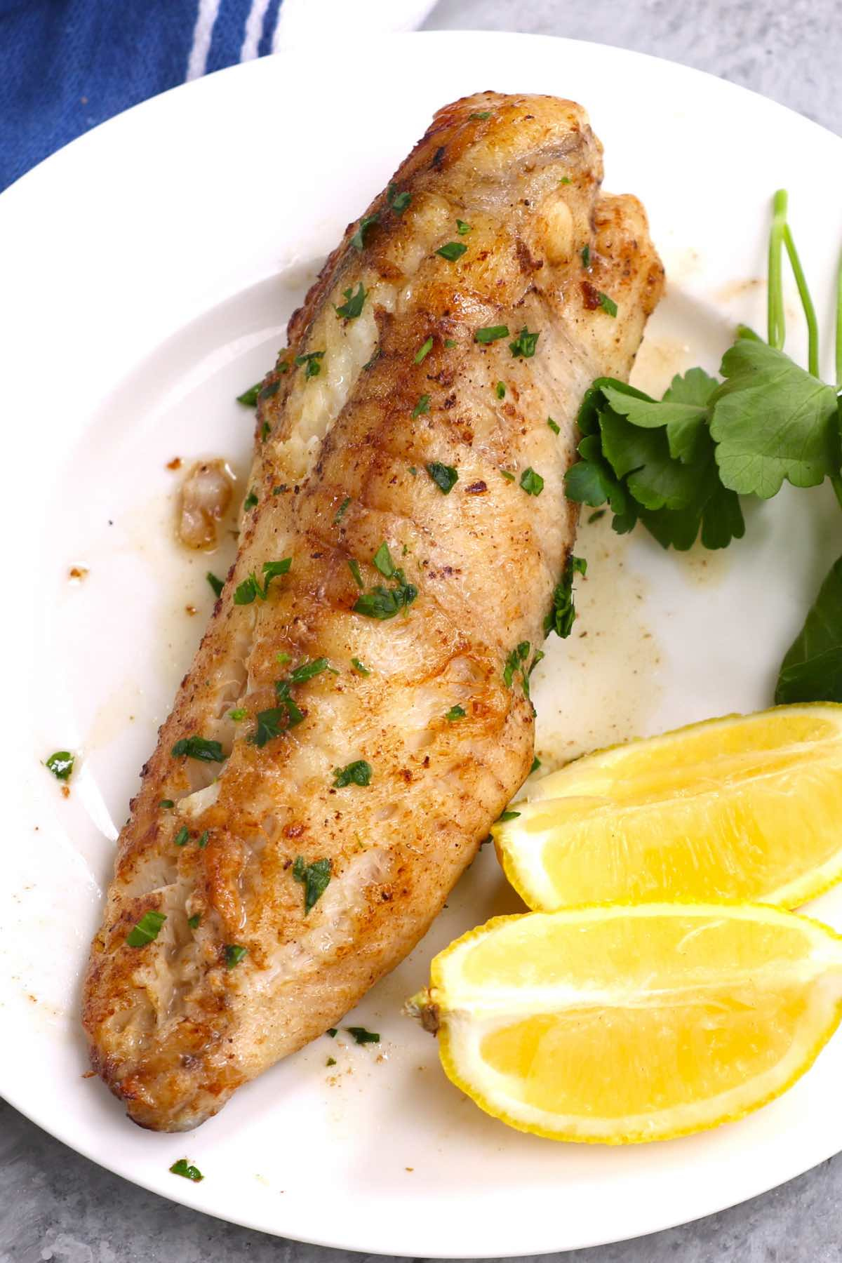 A serving of pan-seared monkfish with lemon and parsley