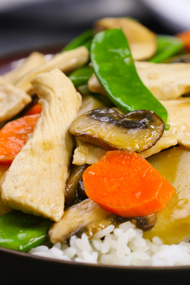 Moo Goo Gai Pan served over rice in a black bowl.