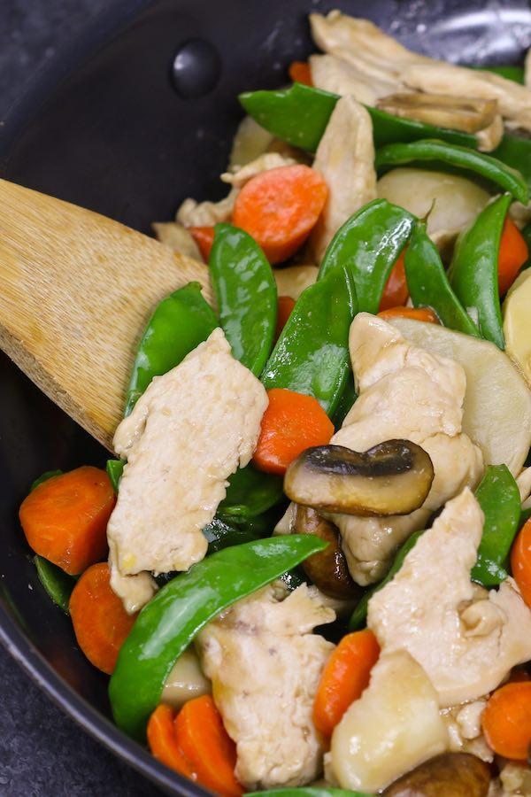 Closeup of Moo Goo Gai Pan ingredients in a wok after stir frying: chicken, mushrooms, water chestnuts, snap peas, carrots