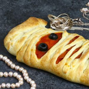 A mummy pizza with jewels for decoration