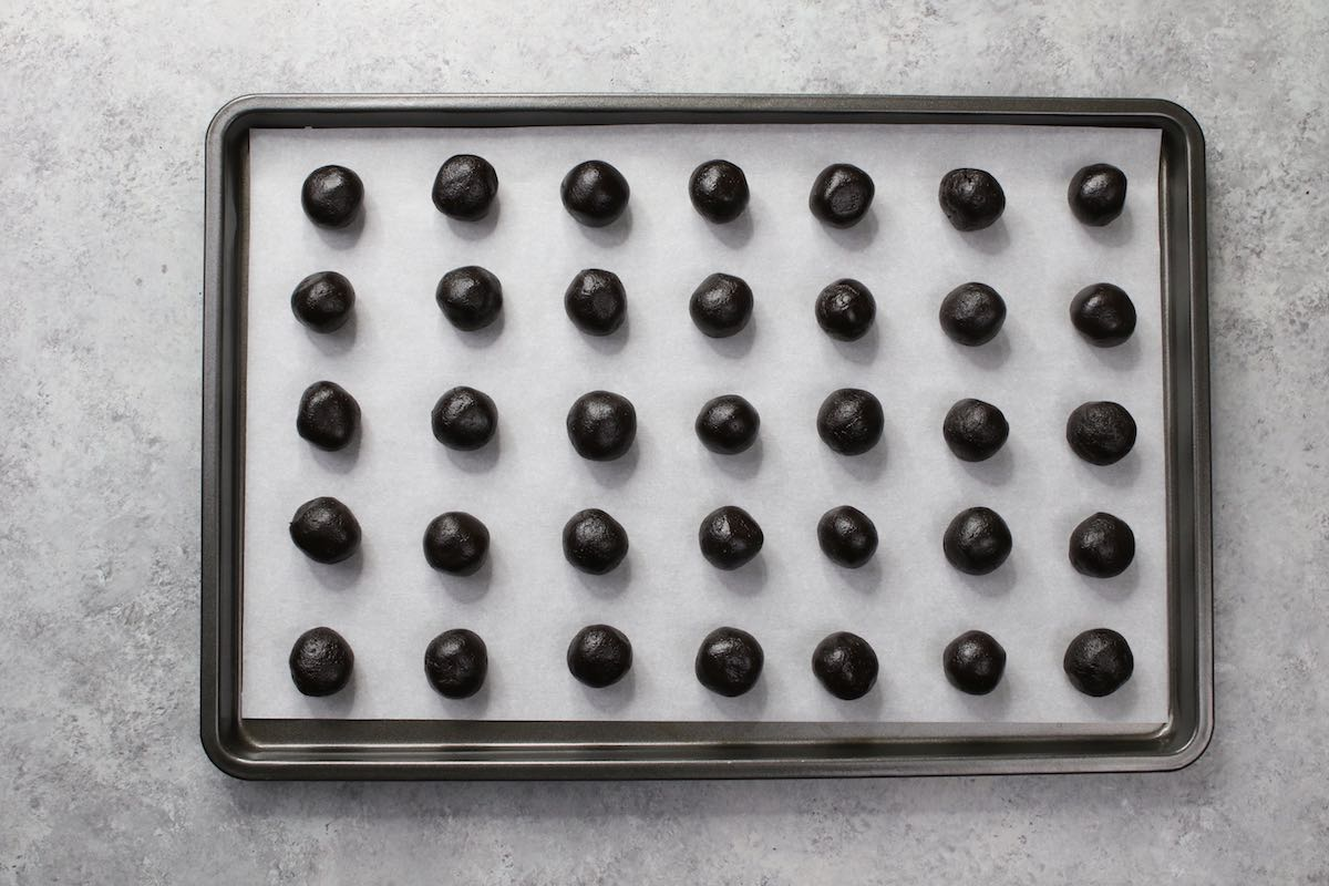 A set of 35 oreo ball fillings on a baking sheet ready to be frozen to firm up