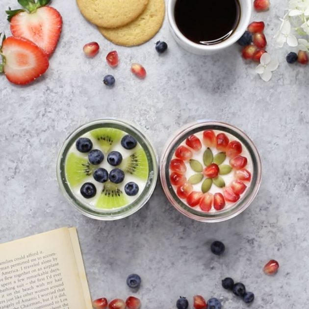 This is an overhead photo of two Oui By Yoplait French-style yogurt pots decorated with fresh fruits, biscuits and a hot beverage for the perfect DIY me moment