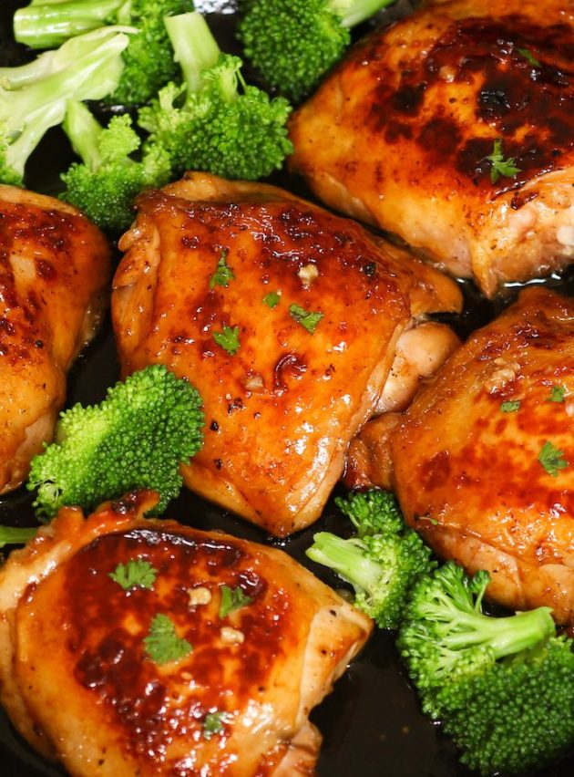 Oven Baked Chicken Thighs with broccoli on a sheet pan after baking, ready to be served. They are juicy, tender and flavorful and easy to make with a few simple ingredients.
