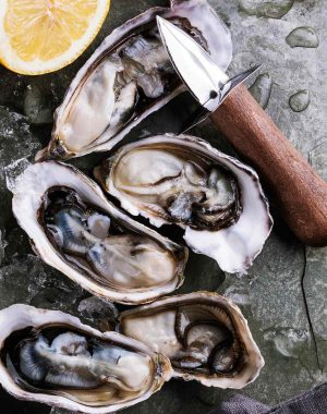 Freshly shucked oysters on ice with lemon wedges