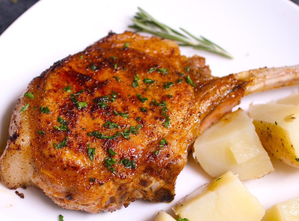 A pan fried pork chop cooked to perfection and garnished with fresh parsley and potatoes on the side on a serving plate