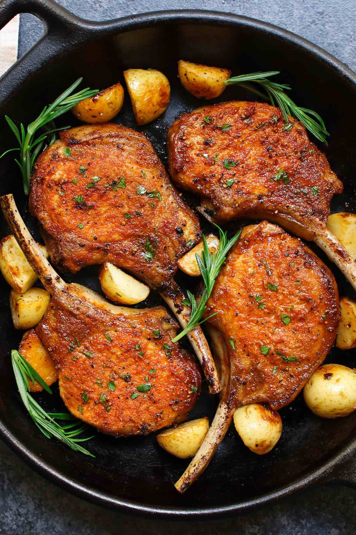 Tender and juicy pan fried pork chops in a cast iron skillet with sprigs of fresh rosemary and sauteed potatoes