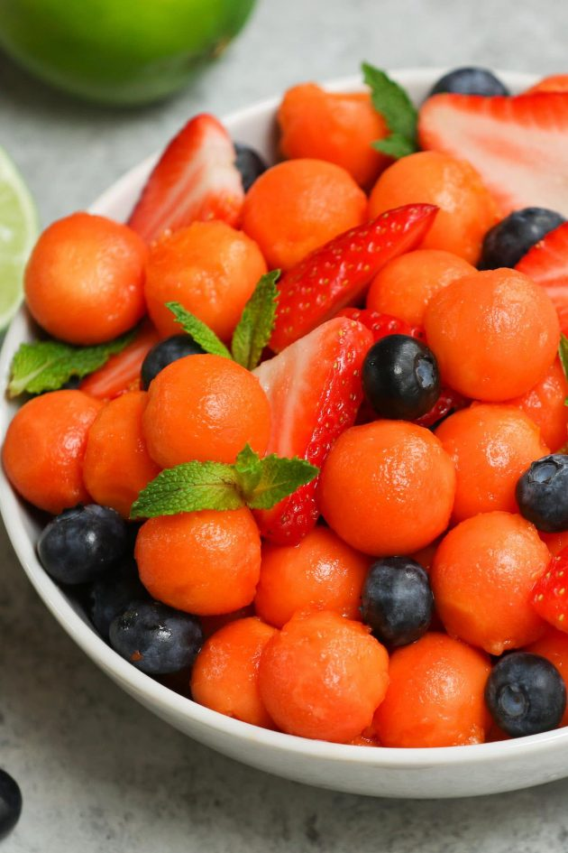 A bowl of freshly cut papaya with berries and mint sprigs
