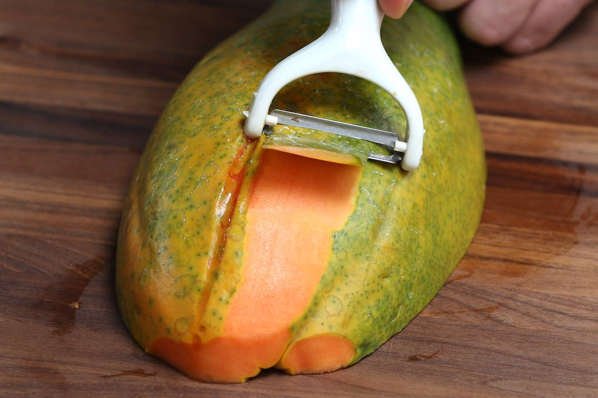 Using a vegetable peeler to remove a papaya's skin
