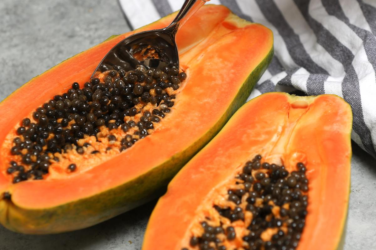 Cut papaya showing the orange flesh and dark seeds