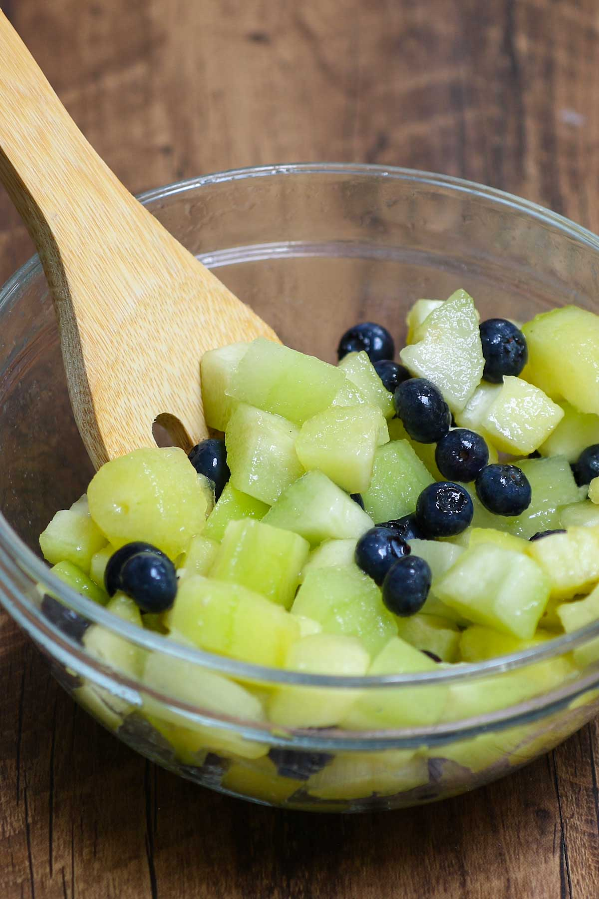 Mixing pepino melon with blueberries and lime juice for a refreshing fruit salad
