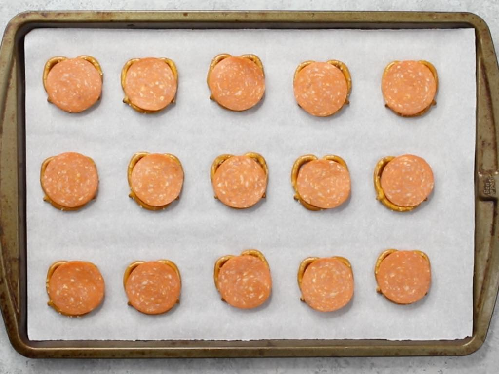 This photo shows pepperoni pizza pretzels arranged on a baking sheet lined with parchment paper