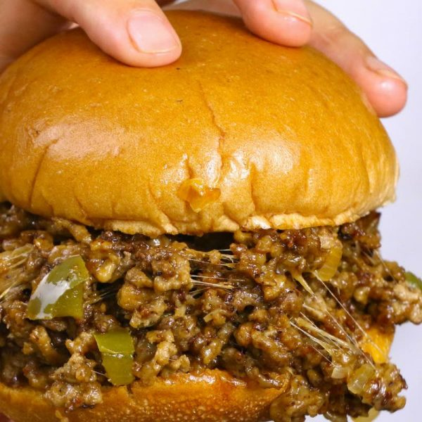 Philly Cheesesteak Sloppy Joes: this photo is a closeup view of this cheesy sandwich held in a hand and about to be eaten