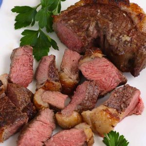 Picanha steak cooked medium on a serving platter with parsley