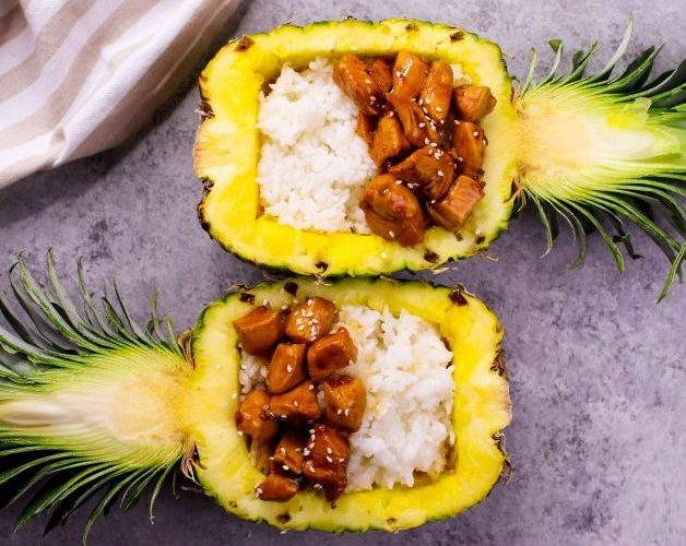 Overhead view of teriyaki chicken served in a half pineapple with rice