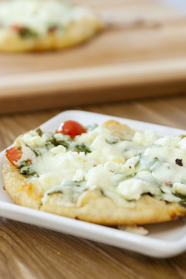 A Greek pita pizza made with spinach, tomatoes and feta cheese on a serving plate hot out of the oven