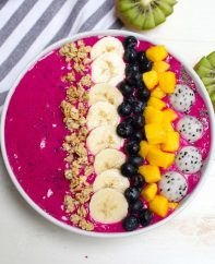 A beautiful pitaya bowl made with frozen dragon fruit, fresh bananas and almond milk with toppings including fresh mango, banana, granola and blueberries