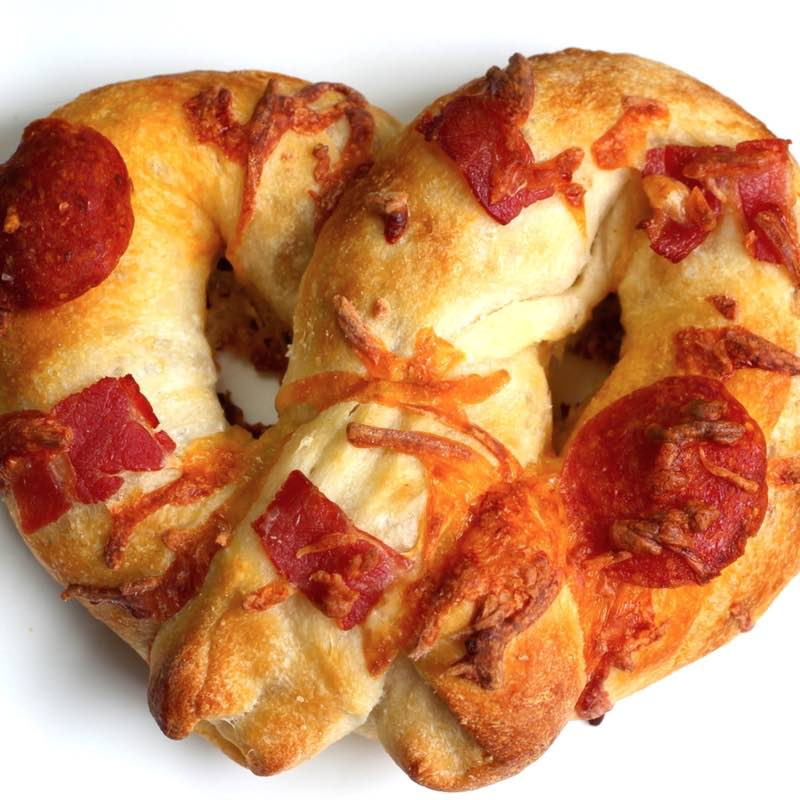 Homemade pizza pretzel with pepperoni, sausage and bacon