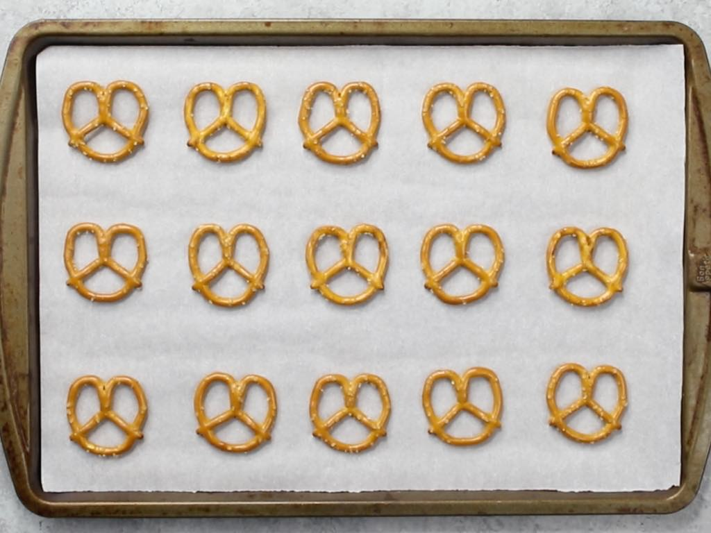 This photo shows pretzels arranged on a baking sheet lined with parchment paper