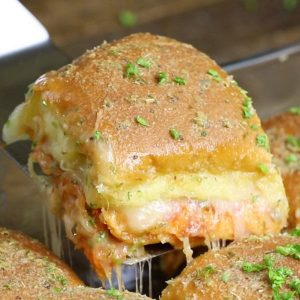 Closeup of pizza sliders fresh out of the oven with a cheese pull