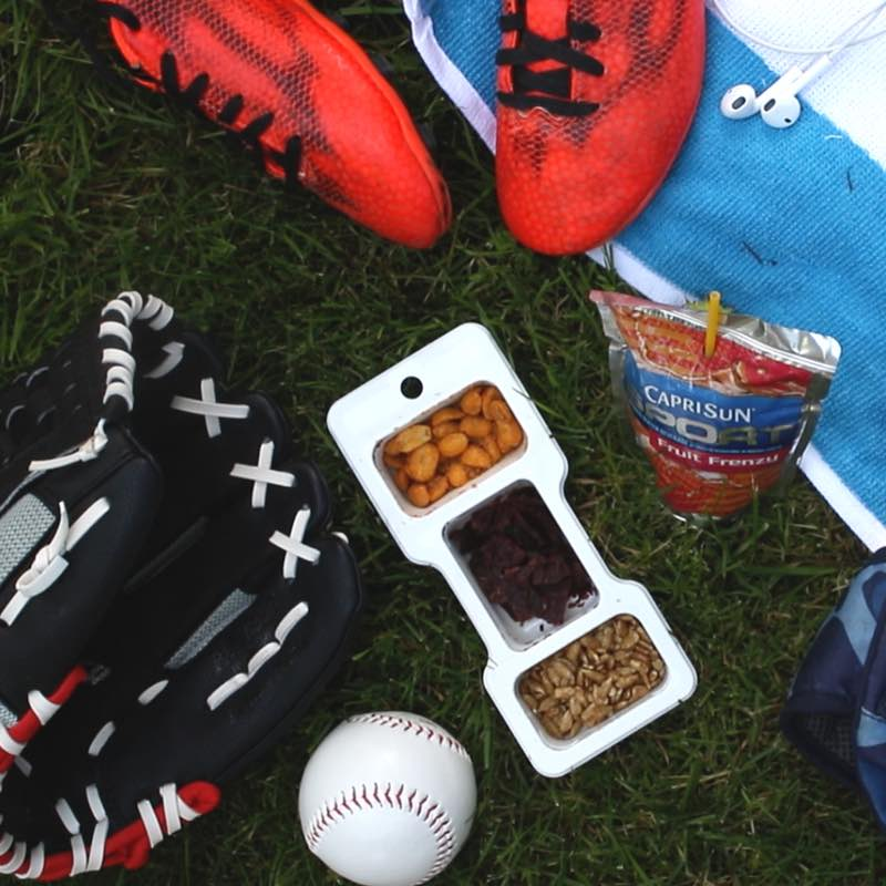 This photo shows enjoying a Planters P3 snack and Capri Sun Sport drink as part of a snack combo during a kids baseball game