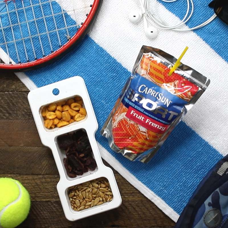 This photo shows enjoying a Planters P3 snack and Capri Sun Sport drink as part of a snack combo during a kids tennis match