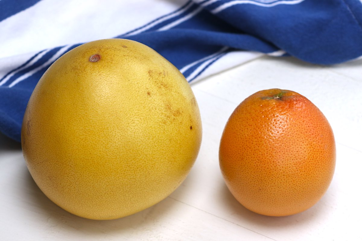 Side by side view of pomelo and grapefruit.