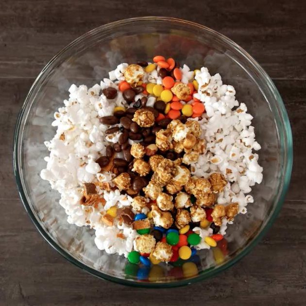Mixing popcorn and candy together in mixing bowl when making Popcorn Cake