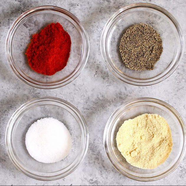 Paprika, garlic powder, salt and black pepper in small bowls