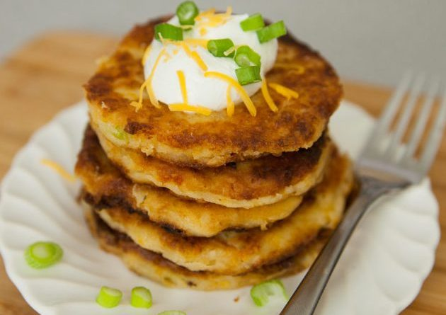A stack of Mashed Potato Pancakes garnished with sour cream and green onions