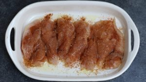 Fajita seasoning on chicken breasts in a baking dish