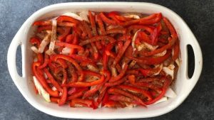 Onions and bell peppers on top of seasoned meat in a baking dish