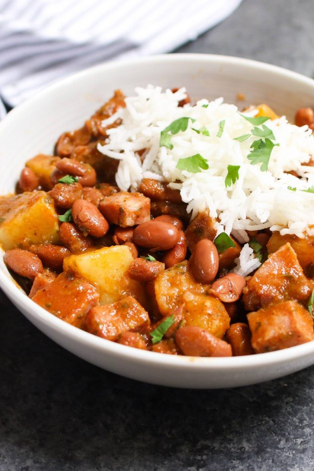 Puerto Rican Rice and Beans are thick, creamy and flavorful! The tender beans are simmered in a sofrito and tomato based sauce, then served over rice. It's a Puerto Rican staple, also known as Habichuelas Guisadas or stewed beans.
