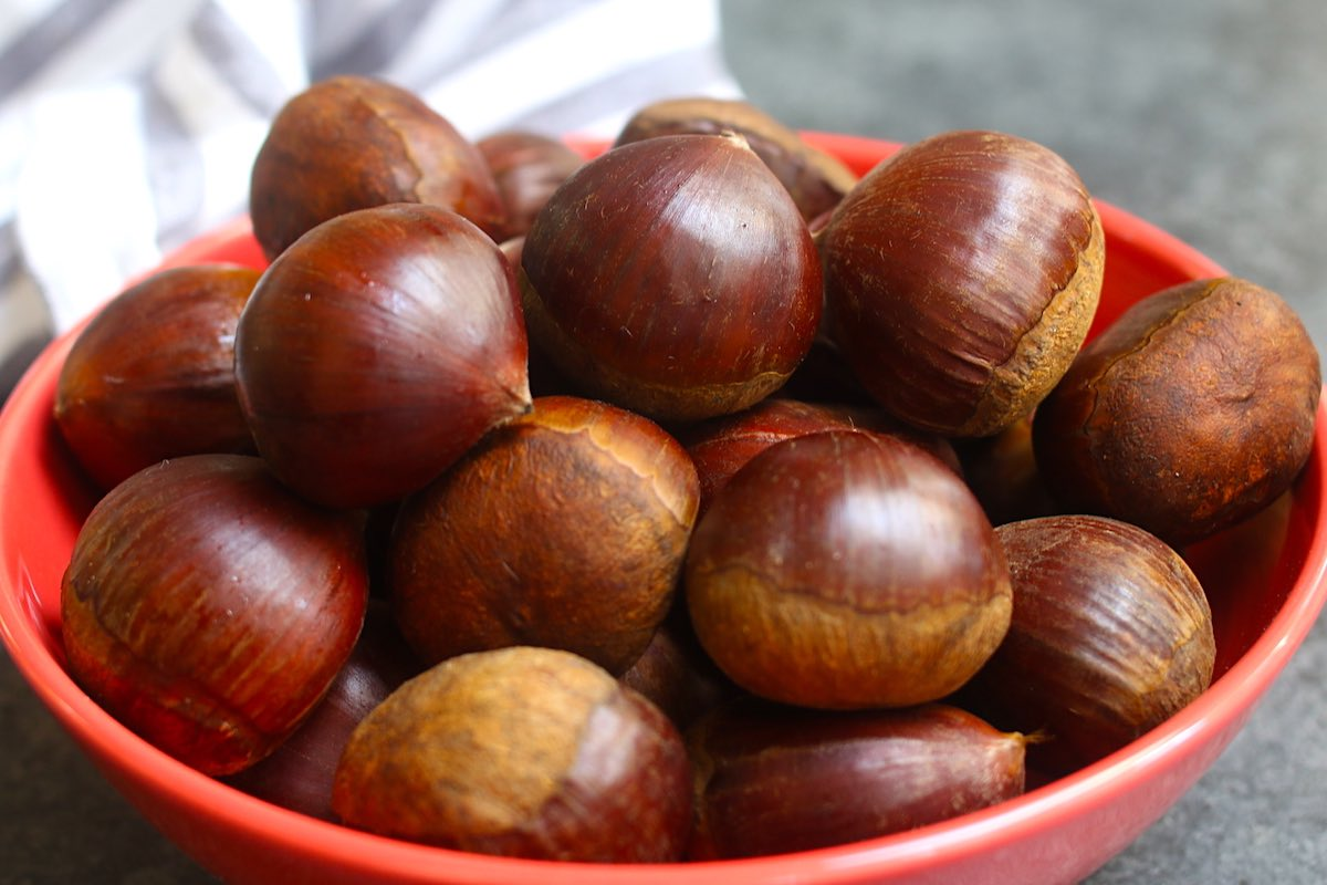 Fresh raw chestnuts in a red bowl.