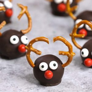 Reindeer Oreo Truffles consist of oreo cheesecake balls coated in dark chocolate and decorated in a reindeer theme for a cute holiday party treat or gift idea