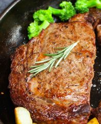 A traditional rib eye steak in a cast iron pan after being pan seared, with broccoli and sauteed potatoes on the side ready for serving